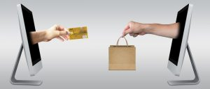 Hand Passing Credit Card while another hand passes a shopping bag